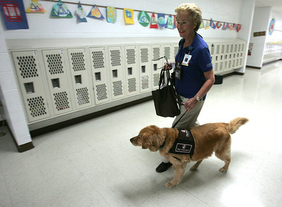 H. Rick Bamman -hbamman@shawmedia.com  Therapy dog owner Patty Reigle of Woodstock and her Golden Retriever Carly walk to a classroom at Jefferson Elementary School in Harvard.