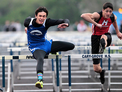 Kyle Grillot - kgrillot@shawmedia.com   Woodstock senior Tyler Parsons competes with Huntley sophomore Brennan Bell during the final men's 110-meter high hurdles event of the Fox Valley Conference boys track meet Friday at Cary-Grove High School.