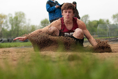 Kyle Grillot - kgrillot@shawmedia.com   Prairie Ridge sophomore Brenden Bruhnke lands after competing in the long jump event during the Fox Valley Conference boys track Friday at Cary-Grove High School.