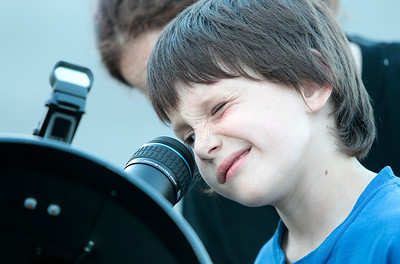 Kyle Grillot - kgrillot@shawmedia.com   Tyler Pierce, 6, looks at the moon through a telescope Tuesday outside the McHenry Public Library. The Lake County Astronomy Society brings their telescopes to various places including the McHenry Public Library for people to stop in and use them.