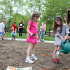 Students at Western Elementary School in Geneva, including first-graders Josey Pelka (left) and Katie Wilson (center), plant their Edible Schoolyard Friday. The garden will include heirloom pumpkins, gourds and carrots. Much of the garden was donated by Great Impressions, a division of Sebert Landscaping, Geneva resident Jay Womack, a landscape architect, Paveloc and Midwest Groundcovers.