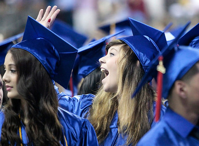 Kyle Grillot - kgrillot@shawmedia.com   Rylee Ann Fava waves to the crowd after entering the arena of the Sears Centre during the Thirtieth Annual Dundee-Crown Commencement Saturday.