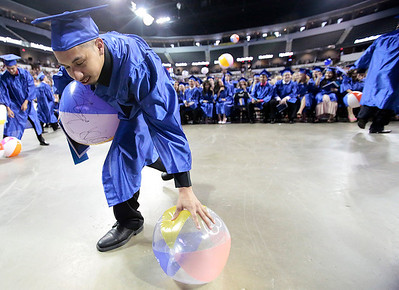 Kyle Grillot - kgrillot@shawmedia.com   Francis Andrade-Montalvo picks up beach balls as others are thrown through the crowd of graduates during the Thirtieth Annual Dundee-Crown Commencement Saturday at the Sears Centre.