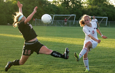 Kyle Grillot - kgrillot@shawmedia.com   Huntley junior Abigail Nordeen kicks the ball past Barrington senior Molly Pfeiffer during the second half of the girls regional soccer game at Jacobs high school Tuesday.