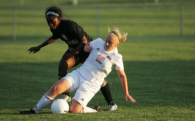 Kyle Grillot - kgrillot@shawmedia.com   Huntley sophomore Deanna Hecht slide to control the ball against the defense of Barrington junior Gabby McLaurin during the first half of the girls regional soccer game at Jacobs high school Tuesday.