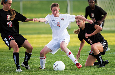 Kyle Grillot - kgrillot@shawmedia.com   Huntley sophomore Katie Constantino (center) fights to control the ball against the defense of Barrington seniors Annalise Avers (left) and Emily Morin during the first half of the girls regional soccer game at Jacobs high school Tuesday.