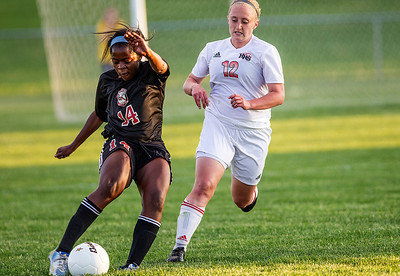 Kyle Grillot - kgrillot@shawmedia.com   Huntley sophomore Deanna Hecht loses control the ball against the defense of Barrington junior Gabby McLaurin during the second half of the girls regional soccer game at Jacobs high school Tuesday.