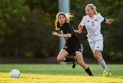 Kyle Grillot - kgrillot@shawmedia.com   Huntley junior Abigail Nordeen chases down Barrington sophomore Kelsey Muniz during the second half of the girls regional soccer game at Jacobs high school Tuesday.