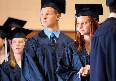 Kyle Grillot - kgrillot@shawmedia.com   Meghan Bennet looks out the doorway of the Cary-Grove gymnasium before the start of the Cary-Grove High School commencement Saturday at Al Bohrer Athletic Field.