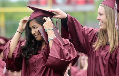 Kyle Grillot - kgrillot@shawmedia.com   Alison Alcazar is helped with her cap by Kailey Aldridge during the Prairie Ridge High School commencement Saturday at the Prairie Ridge football field.