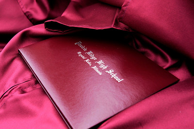Kyle Grillot - kgrillot@shawmedia.com   A diploma rests on the lap of a recent graduate during the Prairie Ridge High School commencement Saturday at the Prairie Ridge football field.