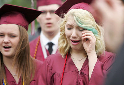 Kyle Grillot - kgrillot@shawmedia.com   Bridget Nugent wipes away tears while singing with the choir during the Prairie Ridge High School commencement Saturday at the Prairie Ridge football field.
