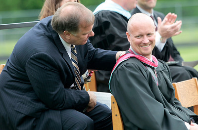 Kyle Grillot - kgrillot@shawmedia.com   District 155 School Board President Ted Wagner talks with Prairie Ridge Principal Paul Humpa while board member Dave Secrest gives a speech regarding Humpa's accomplishments as principal during the Prairie Ridge High School commencement Saturday at the Prairie Ridge football field.