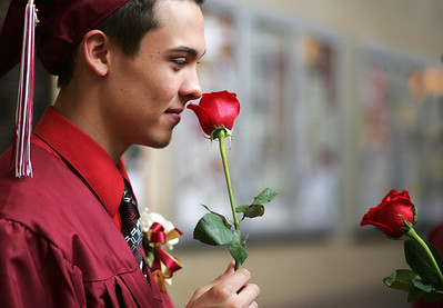Kyle Grillot - kgrillot@shawmedia.com   Graduate Travis Knigge smells his rose before the start of the Richmond-Burton Community High School commencement on Sunday, May 26, 2013.