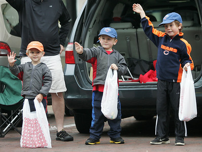 Kyle Grillot - kgrillot@shawmedia.com   Ryan Foster, 3, Nathan Foster, 5, and Owen Foster 7, wave at passing cars during the Woodstock Memorial Day parade at Woodstock Square Monday, May 27, 2013.