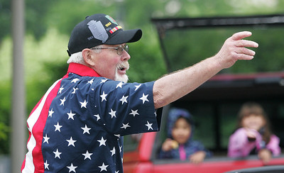 Kyle Grillot - kgrillot@shawmedia.com   Vietnam veteran John Hansen throws candy during the Woodstock Memorial Day parade at Woodstock Square Monday, May 27, 2013.