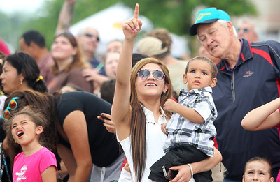 Kyle Grillot - kgrillot@shawmedia.com   Adriana Rubi holds her nephew Jayden Rubi as a stunt man flies over the crowd during the 72nd annual Milk Day parade in in downtown Harvard on Saturday, June 1, 2013.