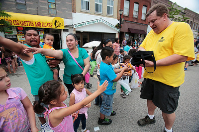 Kyle Grillot - kgrillot@shawmedia.com   Skip Bellon (right) hands out candy top children along Ayers St. during the 72nd annual Milk Day parade in in downtown Harvard on Saturday, June 1, 2013.