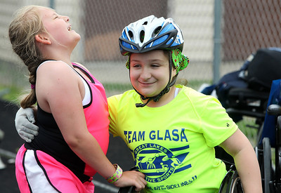 Kyle Grillot - kgrillot@shawmedia.com   Amanda Becker, 8, receives a hug from Gabi Berthiaume, 10, during the sixth annual Run and Roll Track Meet, a Paralympic Experience at McHenry High School's McCracken Field on Saturday, June 1, 2013. This is the last event in the area to qualify for the National Junior Disability Championships in Rochester, Minnesota.\