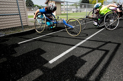 Kyle Grillot - kgrillot@shawmedia.com   Evelyn Felipex, 15, and Gabi Berthiaume, 10 warm up before competing in the sixth annual Run and Roll Track Meet, a Paralympic Experience at McHenry High School's McCracken Field on Saturday, June 1, 2013. This is the last event in the area to qualify for the National Junior Disability Championships in Rochester, Minnesota.