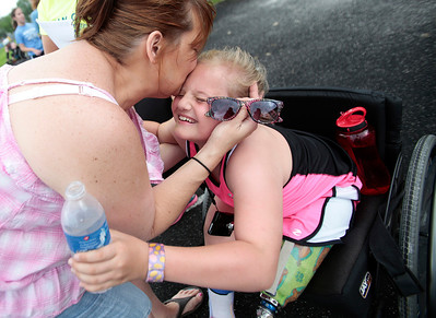Kyle Grillot - kgrillot@shawmedia.com   Pam Becker kisses her daughter Amanda Becker, 8, after competing in the 60-meter dash of the sixth annual Run and Roll Track Meet, a Paralympic Experience at McHenry High School's McCracken Field on Saturday, June 1, 2013. This is the last event in the area to qualify for the National Junior Disability Championships in Rochester, Minnesota.\