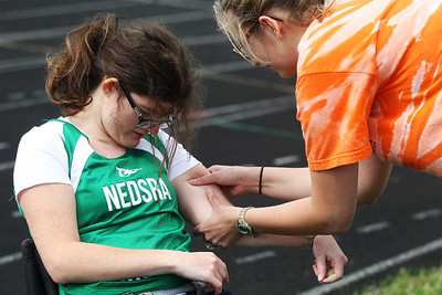 Kyle Grillot - kgrillot@shawmedia.com   Michele Lynch is helped with muscle cramps by coach Maggie Wood-Davis after competing in the 200-meter dash during the sixth annual Run and Roll Track Meet, a Paralympic Experience at McHenry High School's McCracken Field on Saturday, June 1, 2013. This is the last event in the area to qualify for the National Junior Disability Championships in Rochester, Minnesota.