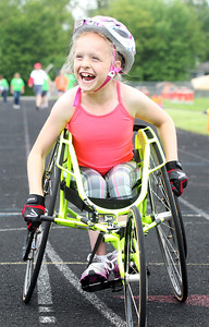 Kyle Grillot - kgrillot@shawmedia.com   Sarah Bolton, 9, laughs after stopping prematurely during the 100-meter dash during the sixth annual Run and Roll Track Meet, a Paralympic Experience at McHenry High School's McCracken Field on Saturday, June 1, 2013. This is the last event in the area to qualify for the National Junior Disability Championships in Rochester, Minnesota.