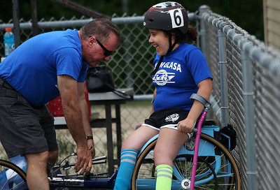 Kyle Grillot - kgrillot@shawmedia.com   Evelyn Felipex, 15, is helped by her father Jon Felipez before competing in the sixth annual Run and Roll Track Meet, a Paralympic Experience at McHenry High School's McCracken Field on Saturday, June 1, 2013. This is the last event in the area to qualify for the National Junior Disability Championships in Rochester, Minnesota.