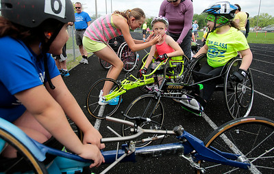Kyle Grillot - kgrillot@shawmedia.com   Elysia Bolton, 13, (center left) helps her sister Sarah Bolton, 9, (center right) by wiping chocolate off her face during the sixth annual Run and Roll Track Meet, a Paralympic Experience at McHenry High School's McCracken Field on Saturday, June 1, 2013. This is the last event in the area to qualify for the National Junior Disability Championships in Rochester, Minnesota.