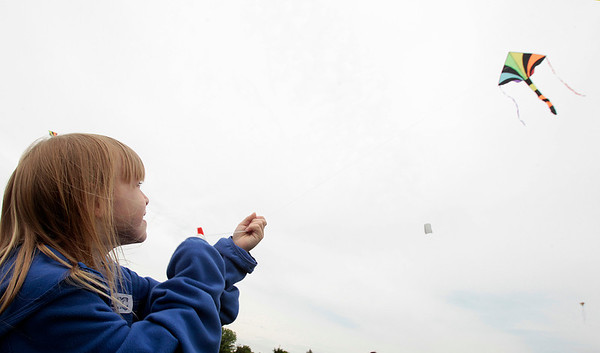 Kyle Grillot - kgrillot@shawmedia.com   Chloe Massaro, 7, flies a kite during the kite festival Sunday at Lippold Park. The first 250 children receive a free kite kit and a demonstration on how to assemble the kite with a help from Chicago Kite Experts.