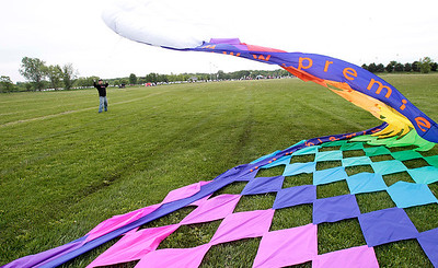 Kyle Grillot - kgrillot@shawmedia.com   Troy Stringer lifts a large kite into the air during the kite festival Sunday at Lippold Park. The first 250 children receive a free kite kit and a demonstration on how to assemble the kite with a help from Chicago Kite Experts.