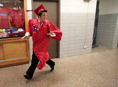 Kyle Grillot - kgrillot@shawmedia.com   Graduate Robert O'Brien rushes to the gymnasium before the start of the Marian Central Catholic High School commencement Friday May 31, 2013.