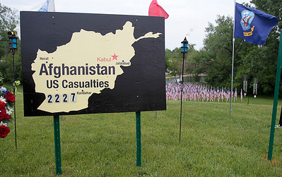 Kyle Grillot - kgrillot@shawmedia.com   Wreaths, signs, and banners line Northwest Highway at the Memorial Day vigil at Lake Julian. The 48-hour vigil displays 322 American flags representing the 322 soldiers from Illinois who gave their lives during the Iraq and Afghanistan conflicts. The vigil has been organized by by the Veterans Network Committee of Northern Illinois and will have a closing ceremony on Memorial Day at 6 p.m.