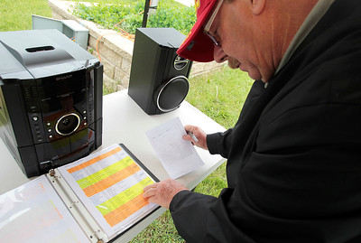 Kyle Grillot - kgrillot@shawmedia.com   Veterans Network Committee member Tom Gillis looks through the list of Illinois' deceased at the Memorial Day vigil at Lake Julian. The 48-hour vigil displays 322 American flags representing the 322 soldiers from Illinois who gave their lives during the Iraq and Afghanistan conflicts. The vigil has been organized by by the Veterans Network Committee of Northern Illinois and will have a closing ceremony on Memorial Day at 6 p.m.