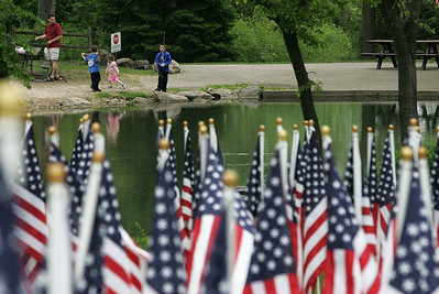 Kyle Grillot - kgrillot@shawmedia.com   Ori Schor and his children Omer, 8, Donna, 3, and Yotemm fish across the lake from the Memorial Day vigil at Lake Julian. The 48-hour vigil displays 322 American flags representing the 322 soldiers from Illinois who gave their lives during the Iraq and Afghanistan conflicts. The vigil has been organized by by the Veterans Network Committee of Northern Illinois and will have a closing ceremony on Memorial Day at 6 p.m.