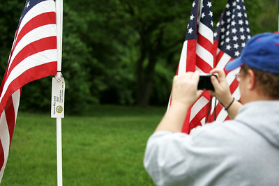 Kyle Grillot - kgrillot@shawmedia.com   Jodi Hogrewe takes a picture of Jason McLeod's flag at the Memorial Day vigil at Lake Julian. The 48-hour vigil displays 322 American flags representing the 322 soldiers from Illinois who gave their lives during the Iraq and Afghanistan conflicts. The vigil has been organized by by the Veterans Network Committee of Northern Illinois and will have a closing ceremony on Memorial Day at 6 p.m.