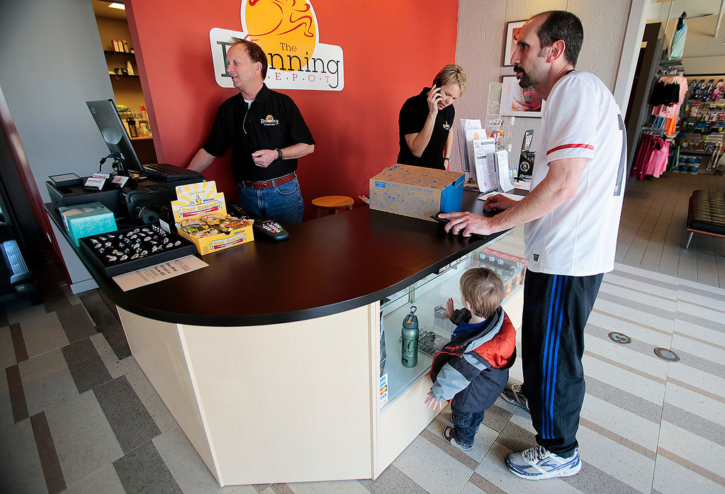 """Kyle Grillot - kgrillot@shawmedia.com   Don Gervais (left) assists customers Doug Carlino with his son Simon Carlino, 2, inside the Running Depot in downtown Crystal Lake on Thursday while owner Pam Andrews answers the phone. """"People come for our knowledge and service, and the value of the process,"""" said Andrews."""