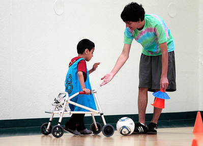 Kyle Grillot - kgrillot@shawmedia.com   John Gayton, 5, of Cary give a high-five to Steven Loke, 17, of Cary during a TOPS soccer practice at Sage Products on Saturday, May 4, 2013. TOPS soccer is a program for children, who have mental or physical disabilities. It was started in the fall of 2012, and provides an opportunity for any child to play soccer. The kids participating have cognitive disabilities such as autism or downs syndrome, or physical disabilities such as cerebral palsy requiring a walker or wheel chair. To help, there are high school students paired up with each kid.