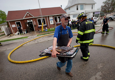 Dan Lisi, carries photos from the Polish Legion of American Veterans Post 188 building after a fire destroyed the building Sunday, May 11, 2014 in McHenry.  John Konstantaras / for the Northwest Herald