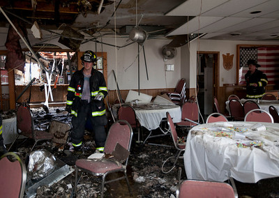 A firefighter walks through Polish Legion of American Veterans Post 188 after a fire destroyed the building Sunday, May 11, 2014 in McHenry.  John Konstantaras / for the Northwest Herald