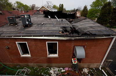 A firefighter inspector takes photos in a window after a fire destroyed Polish Legion of American Veterans Post 188 a Sunday, May 11, 2014 in McHenry. John Konstantaras / for the Northwest Herald
