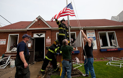 Firefighters help members of the Polish Legion of American Veterans Post 188 lower their flags after a fire destroyed their building Sunday, May 11, 2014 in McHenry.  John Konstantaras / for the Northwest Herald