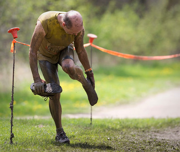 Fred Mooney, 50 from Barrington, adjusts his sock after getting through the Mud Mile obstacle during the Tough Mudder at the Richmond Hunt Club Sunday, May 11, 2014 in Richmond. The event draws 10,000 to 15,000 people to 10-12-mile obstacle courses. John Konstantaras / for the Northwest Herald