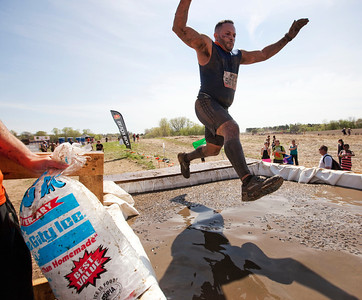A runner jumps into icy water at the Arctic Enema during the Tough Mudder at the Richmond Hunt Club Sunday, May 11, 2014 in Richmond. The event draws 10,000 to 15,000 people to 10-12-mile obstacle courses. John Konstantaras / for the Northwest Herald