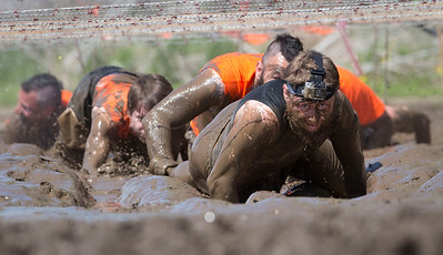 Participants crawl through mud as the hit the Kiss of Mud obstacle during the Tough Mudder at the Richmond Hunt Club Sunday, May 11, 2014 in Richmond. The event draws 10,000 to 15,000 people to 10-12-mile obstacle courses. John Konstantaras / for the Northwest Herald