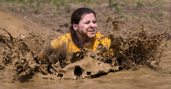 Debbie Robaczewski, 25 from Crystal Lake and a teacher at Harvard high school., splashes into muddy water at the Mud Mile obstacle during the Tough Mudder at the Richmond Hunt Club Sunday, May 11, 2014 in Richmond. The event draws 10,000 to 15,000 people to 10-12-mile obstacle courses. John Konstantaras / for the Northwest Herald