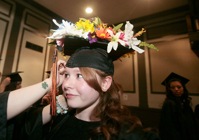 Michelle LaVigne/ For Shaw Media Kalee Cossiboon receives an adjustment to her cap prior to the McHenry East High School's commencement in McHenry on May 15, April 15, 2014.