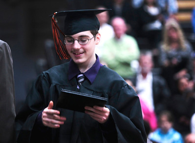 Michelle LaVigne/ For Shaw Media Darrin Gilligan checks out his diploma after receiving it during McHenry East High School's commencement in McHenry on May 15, April 15, 2014.