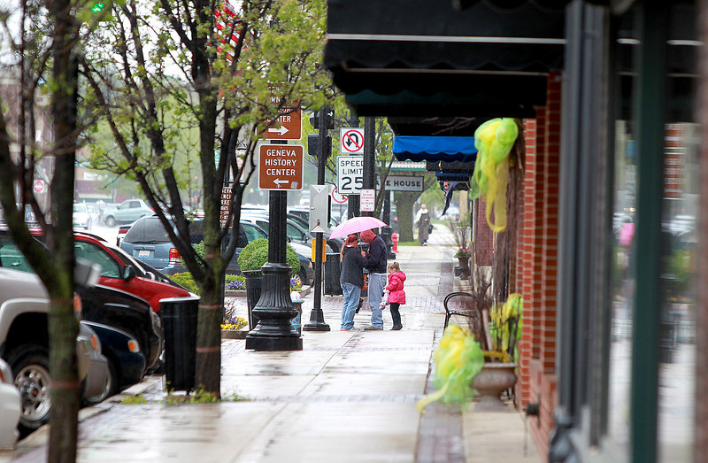 Pedestrians make their way through a mix of snow and freezing rain in downtown Geneva Friday.