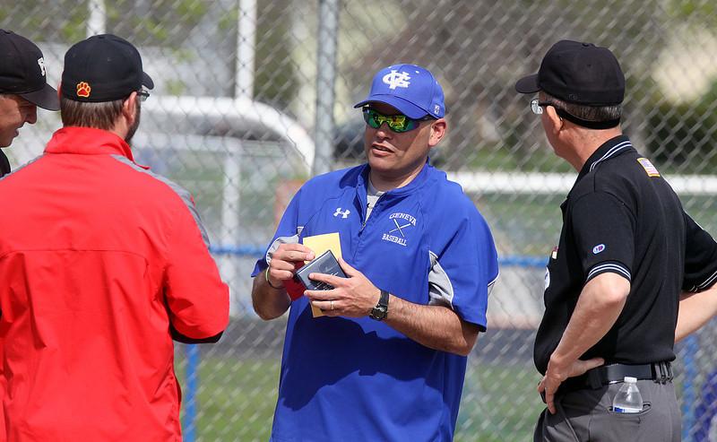 Jeff Krage – For Shaw Media<br /> Geneva varsity baseball head coach Matt Hahn talks with Batavia head coach Matt Holm and umpires before the start of Saturday's doubleheader in Geneva.<br /> Geneva 5/10/14
